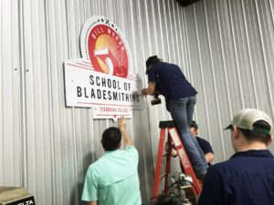 Logo being installed in the new bladesmith shop